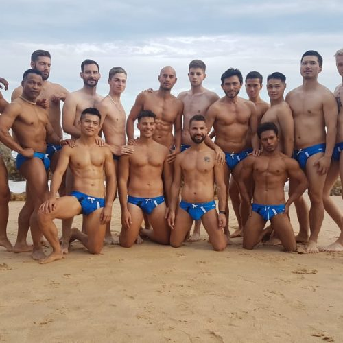 In this photo is a group of very handsome young men who participated in the Mr Gay World 2018 competition. On the photo they are posing as a group on a beach in Niku swimwear. Some are very tanned and some are very light-skinned. They are all very attractive in their own way.