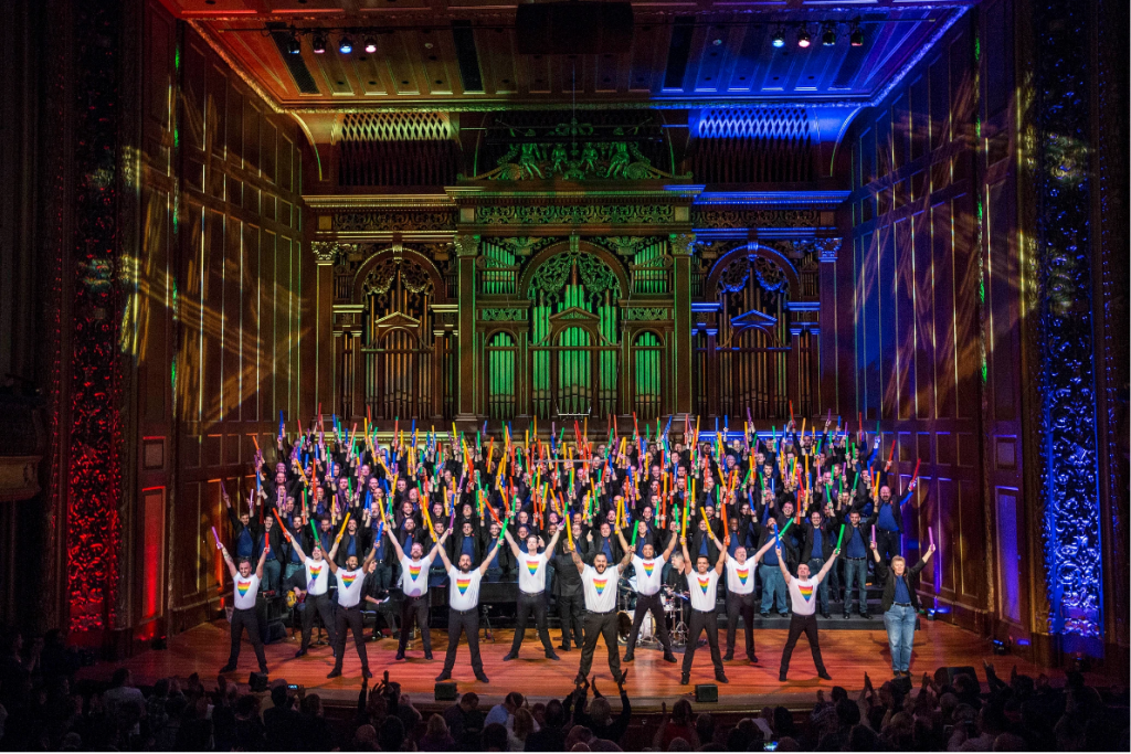 This is a picture of the Boston Gay Mens Chorus on stage, with their arms stretched out above them. There are rainbow coloured lights on the stage.